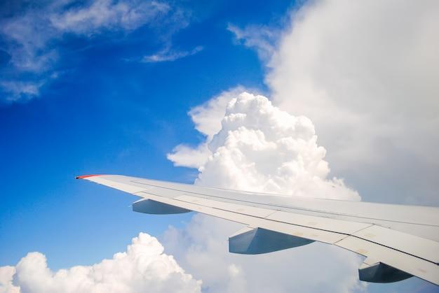 積雲の雲の上に浮かぶ飛行機