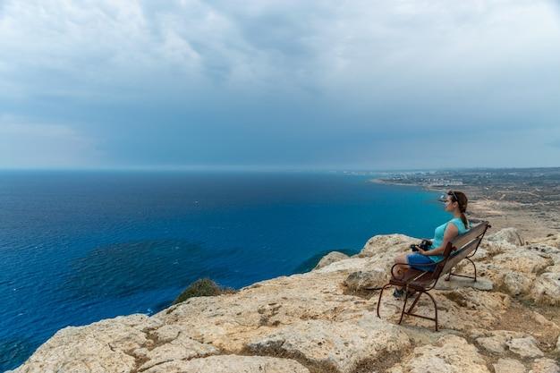 木製のベンチで、若い女の子が海からの風を楽しんでいます。