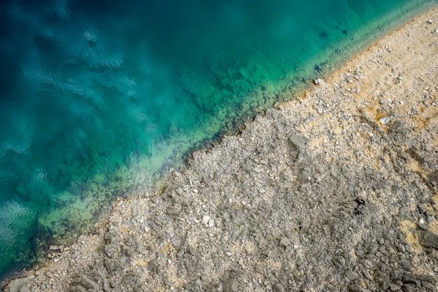 透明な青緑色の水が石の多い海岸に出会う絵のような場所。