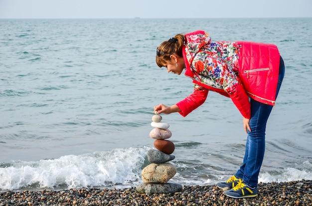 Девушка строит пирамиду из цветных камней на черном море в батуми, грузия.