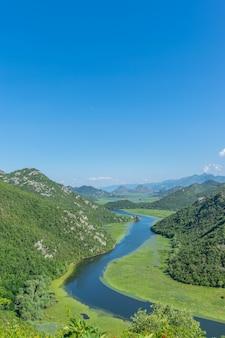 Живописная извилистая река протекает среди зеленых гор.