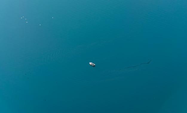 一人の漁師が外洋の真ん中でボートから釣りをしています。