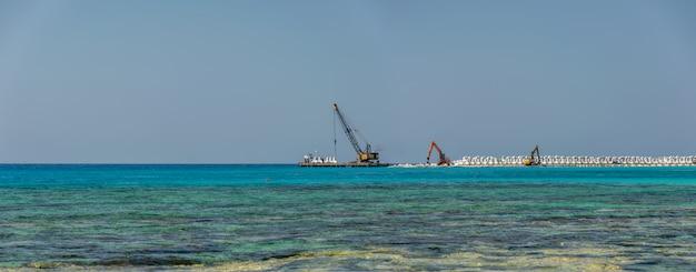 Рабочие строят волнорез на берегу лазурного моря.