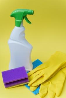 Моющее средство, губка и перчатки для уборки дома на желтом ярком фоне