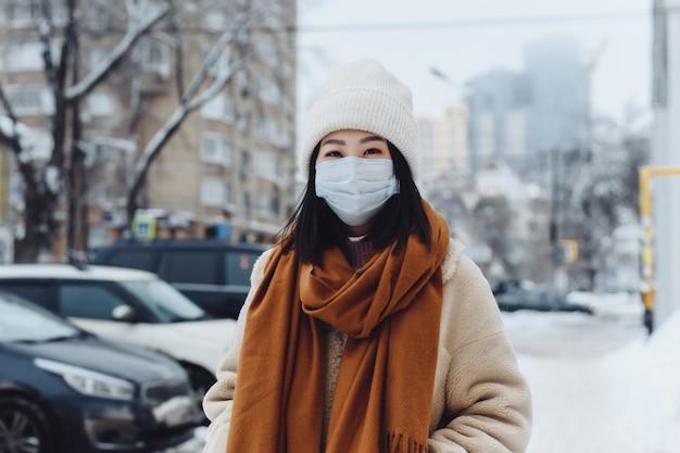 Прохожая азиатская девушка в защитной медицинской маске на открытом воздухе. женщина на улице зимой защищает дыхательные пути от эпидемии коронавируса