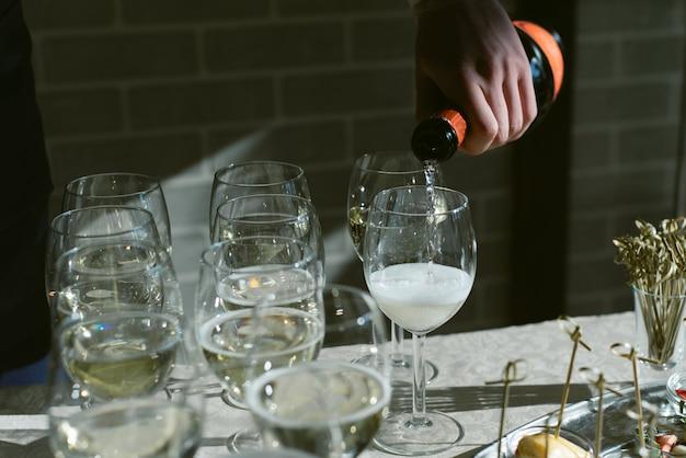 Официант наливает шампанское в бокалы на праздник