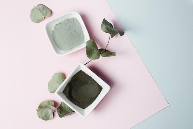 Различные ингредиенты для домашнего ухода за кожей. серая, черная и синяя глина, листья эвкалипта на пастельном фоне. увлажняет и очищает кожу с помощью бальзама и крема. красивая тонировка в одном оттенке