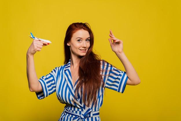 飛行機を押しながら黄色の壁に分離されたポーズブルーストライプのオーバーオールで陽気な若い赤毛の女性の女の子。人々のライフスタイルのコンセプト。