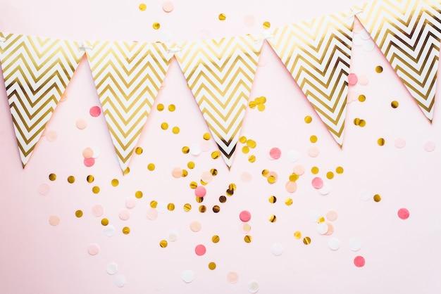 Шаблон для праздников. бумажная гирлянда из флажков на розовом фоне с конфетти