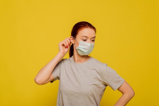 Портрет молодой женщины, носить маску, крупным планом, изолированных на желтой стене. эпидемия гриппа, пылевая аллергия, защита от вирусов. концепция загрязнения воздуха города