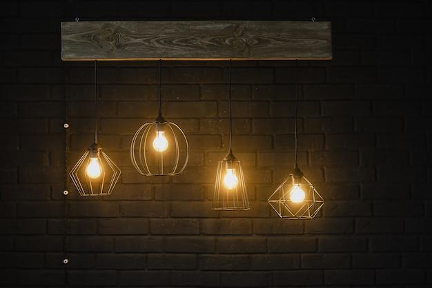コピースペースとレトロなパターン。黒い暗い背景に、暗闇の中で光を放つ美しい神秘的なガラスイエローオレンジ電気白熱灯をクローズアップ