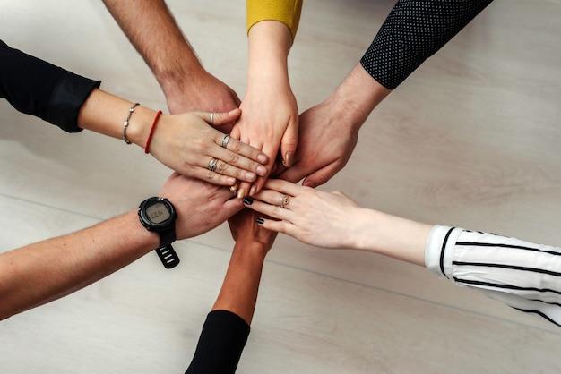 Компания из нескольких человек объединяется в одну команду. командная работа
