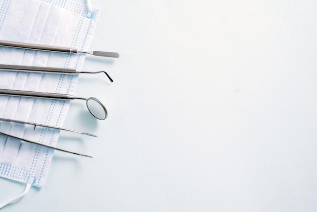 歯科用器具:ミラーと歯科用プローブは明るい青の背景に医療用マスクに左に横たわっています。広告のパターン