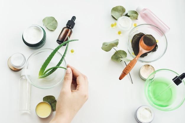 女の子の手が成分を混ぜて、保湿美容液を作ります。白いテーブルの上の天然成分。ブラッククレイ、アロエベラの葉、保湿クリーム、バーム、トニック