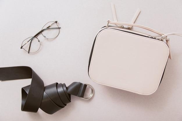 ベージュのテーブルに白いバッグ、黒い革のベルト、ファッショングラス