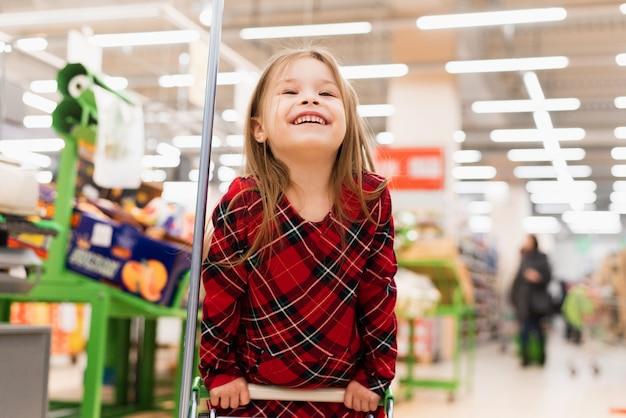 スーパーでグラフを保持している陽気な女の子