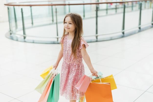 買い物袋と一緒に歩いている陽気な幼児の女の子。お店でポーズの買い物袋を持つ少女の笑顔。店舗での買い物のコンセプト