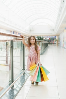 お店でポーズの買い物袋を持つ少女の笑顔。リトルプリンセスの素敵な甘い瞬間、カメラに楽しんでかなりフレンドリーな子