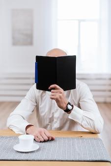 若い男が彼のオフィスで働いています。先生は講義の準備をします。オフィスの木製の机の上のノートで働くデザイナーの手