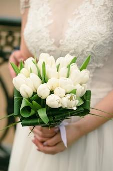 結婚式の日のブライダルブーケ。白いチューリップの花束を持って美しい少女。