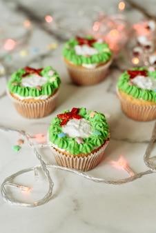 大理石のテーブルに新年のお菓子。マスティックとクリームで飾られたクリスマスカップケーキ