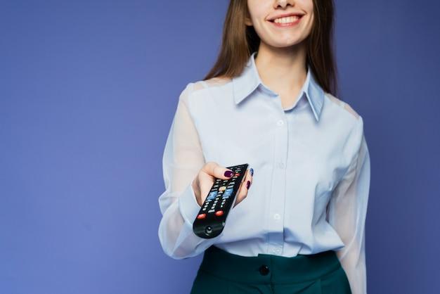 青いシャツを着た幸せな女性がテレビで映画やテレビ番組を見る。薄紫色の背景の美しい少女は、リモコンを使用してチャンネルを切り替えます