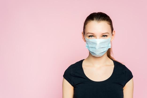 防護マスクの美しい若い女性。コロナウイルスから彼女を守るマスクを持つ少女。コロナウイルスパンデミック
