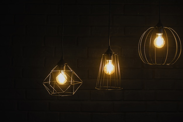 Крупный план лампы накаливания. лампа с оранжевым светом. горящая лампа эдисона накаливания с большой декоративной спиралью