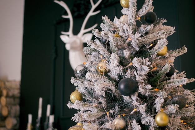 屋内に白い人工雪が入った濃い緑色のクリスマスツリー。金と濃い青の装飾品でゴシック様式のクリスマスツリー。壁に白い鹿と暗いインテリア。新年のコンセプト