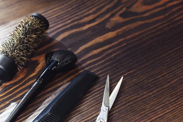 Инструменты парикмахера на деревянной предпосылке. темный оттенок