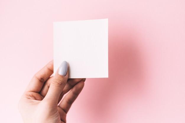 Рука девушки держит пустую белую открытку на белой предпосылке. копировать пространство