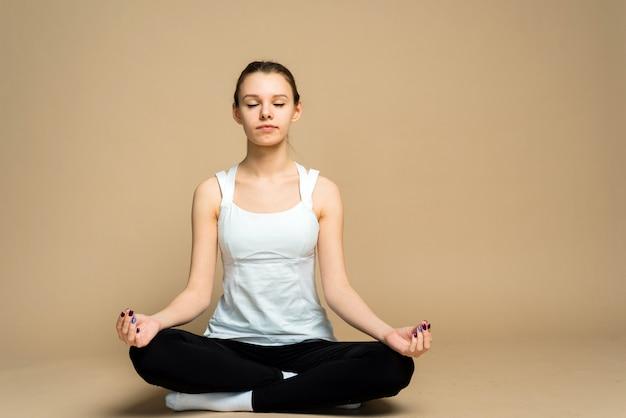 スポーツユニフォームに描かれた髪の女性は、スタジオでヨガをやっています。女の子が蓮華座に座り、目を閉じて瞑想します。家の隔離、家にいる