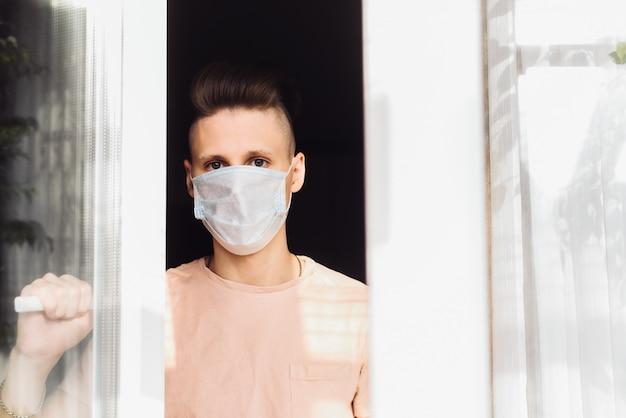 防護マスクでハンサムな若い男が家の窓の外に立っています。パンデミックとコロナウイルス感染のリスクによる自己隔離の呼びかけ