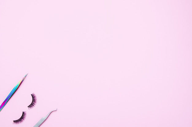 Набор для наращивания ресниц на розовом фоне. понятие красоты, красоты. накладные ресницы и пинцет