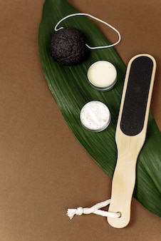 皮膚を剥離するための自然の様々な軽石とヤシの葉は、コピースペースと茶色の背景にあります。クリーム、ローション、またはバームで足の皮膚を保湿するコンセプト