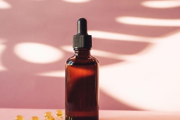 Стеклянная бутылка с увлажняющей сывороткой на розовом фоне с витамин с в капсулах. коричневая бутылка с капельницей на фоне тропической тени пальмового листа. концепция ухода за кожей