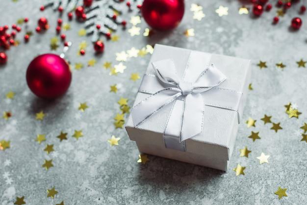 Серебряный подарок с бантом на сером снежном фоне с красными елочными шарами и золотыми звездами конфетти