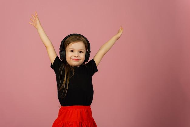 Маленькая девочка слушает музыку в больших наушниках на розовом пастельном фоне и радуется