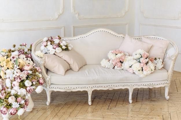 Светло-бежевый диван нежного цвета рядом с большим количеством цветов, роз и пионов
