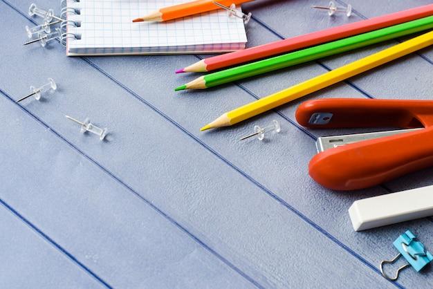 学校および事務用品。色鉛筆と青い木製の背景に学校と学生の教育のためのノート。