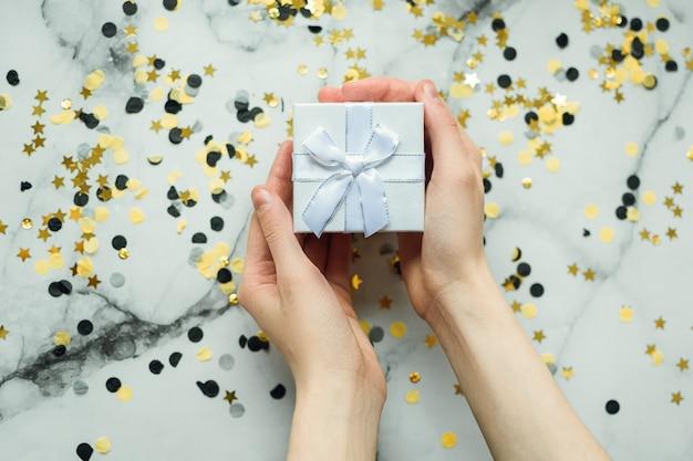 マニキュアなしの女の子の手の中の銀の贈り物