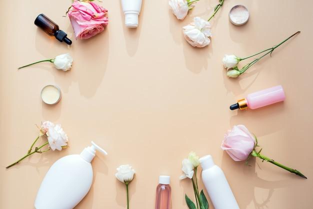 Косметика из натуральных ингредиентов и экстрактов цветов и роз на бежевом фоне.