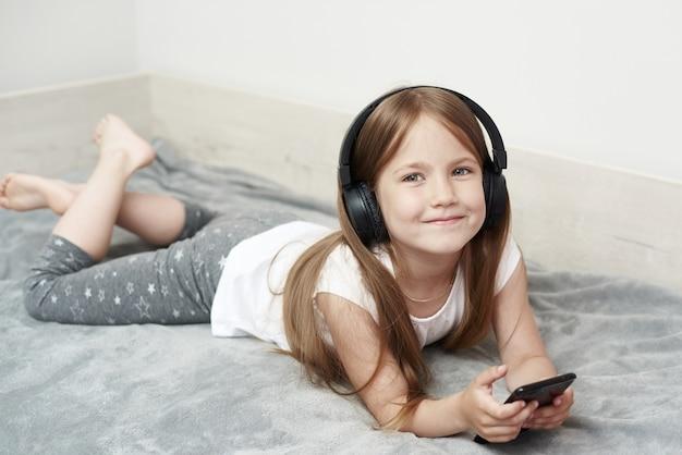 Маленькая девочка в наушниках. девушка слушает музыку. маленькая девочка играет в телефон