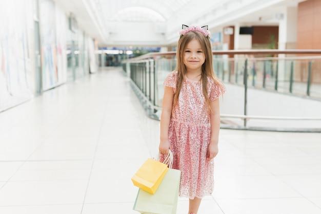 Малыш держит сумки. маленькая девочка в розовом платье, глядя через витрину. улыбающаяся смеющаяся девушка в розовом платье с разноцветными сумками в торговом центре