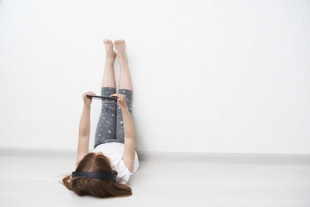 Немного лежит на полу. девушка держит телефон.
