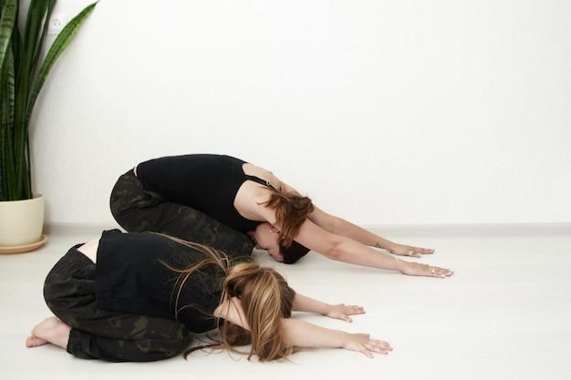 Мать и дочь занимаются йогой. женщина и маленькая девочка находятся в расслабленном положении.