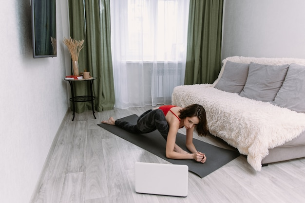 ヨガの板をやって、ラップトップでオンラインチュートリアルを見てフィットの女性