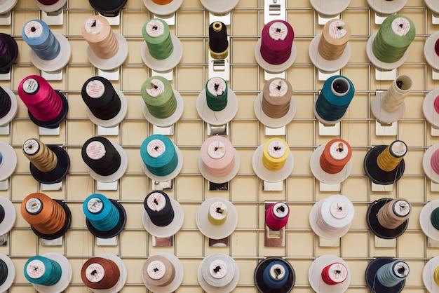 テーラーショップに掛かっている糸のスプール。ミシンのかせが縫製工場に掛かっています。
