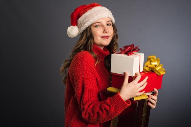サンタクロースの帽子と赤いニットのセーターを着た美しいモデルは、多くの贈り物を手に持っています。