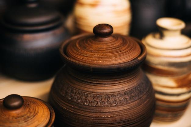 フェアではたくさんの陶器の料理。粘土の国立ロシア料理。焦げた黒い陶器。焼けた土鍋と皿、皿